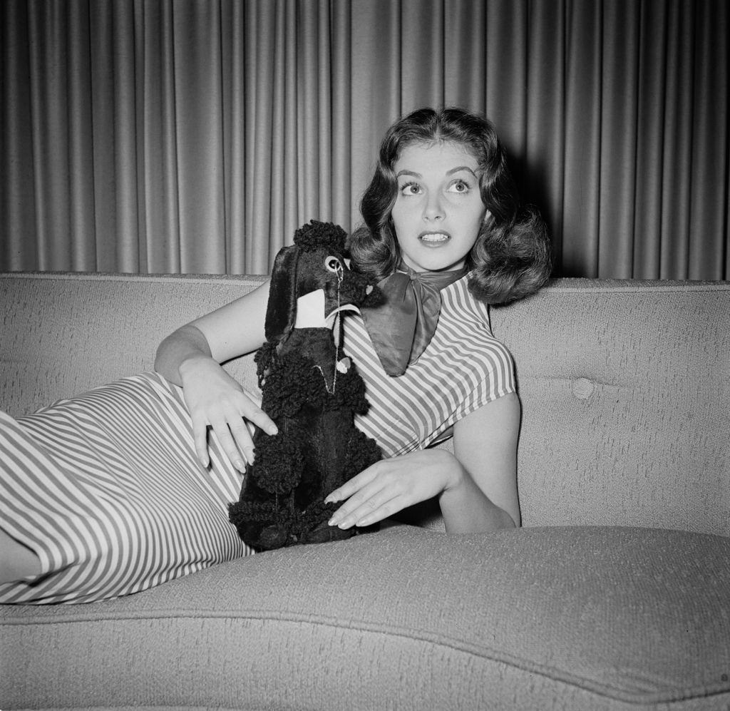 Pier Angeli holding a soft toy poodle with a monocle, 1955