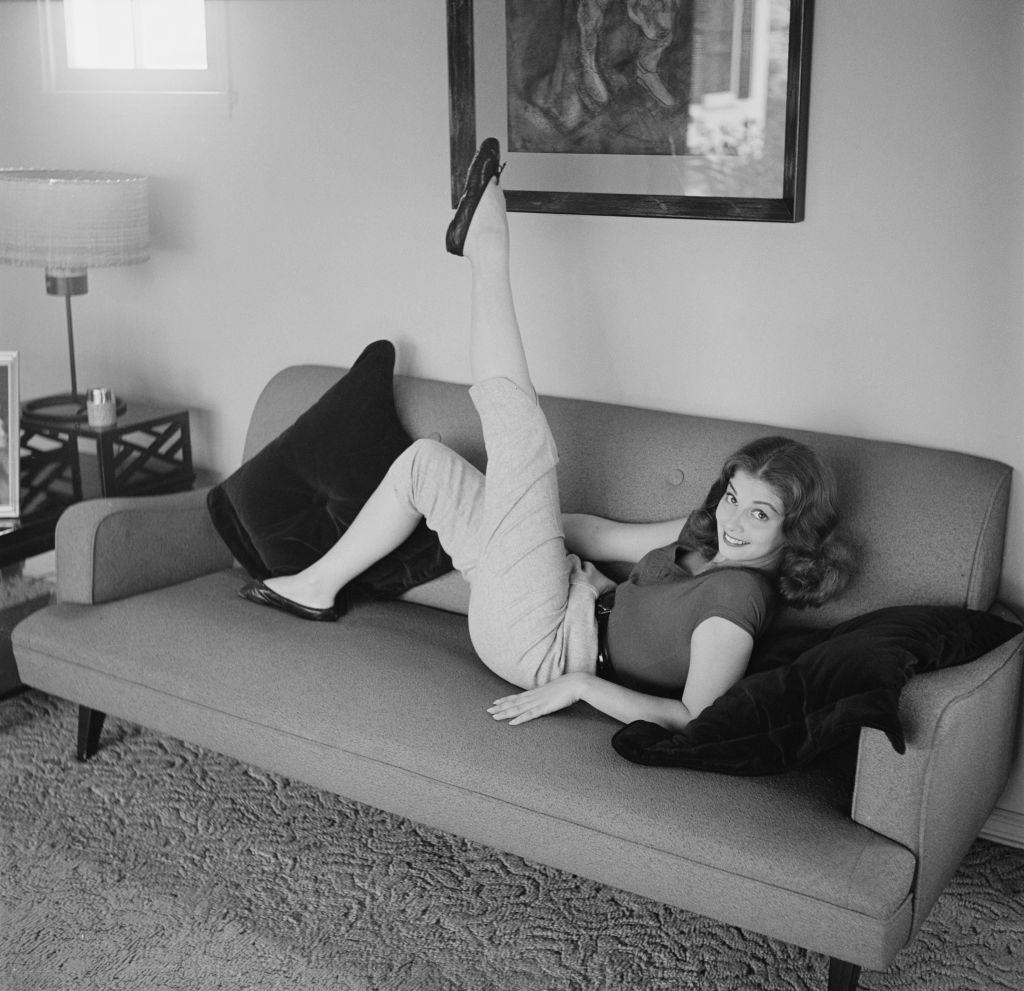 Pier Angeli relaxing on the sofa, 1955