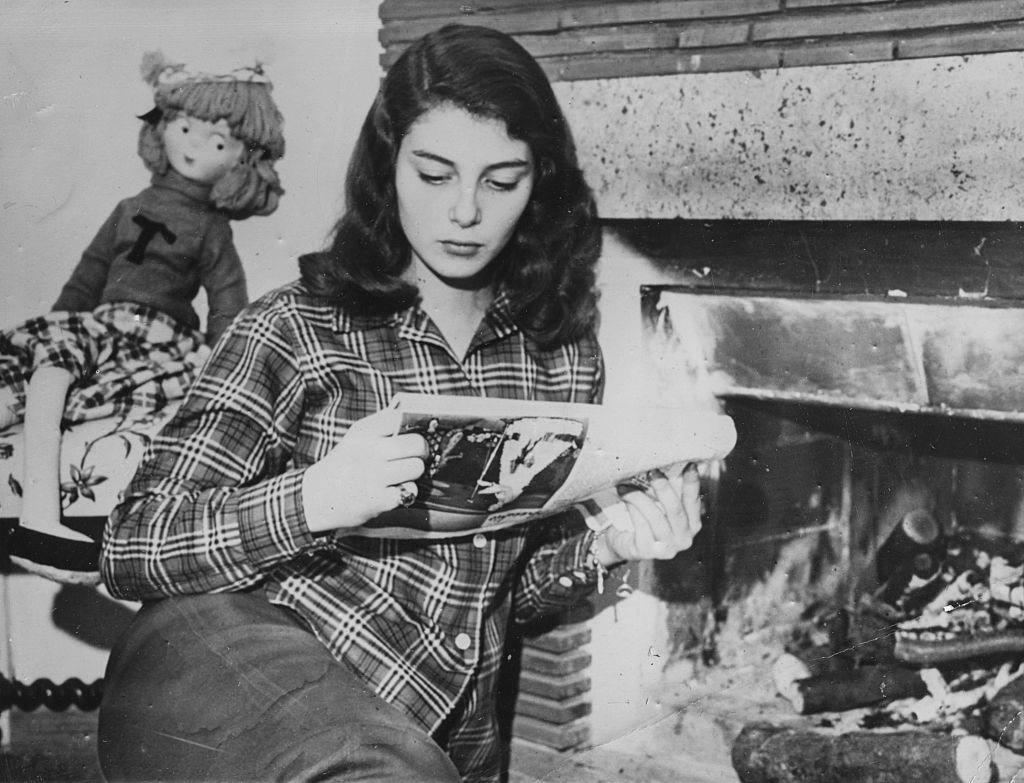 Pier Angeli reading a newspaper by the fire, after being given a five year contract in Hollywood by Metro Goldwyn Mayer, circa 1950.