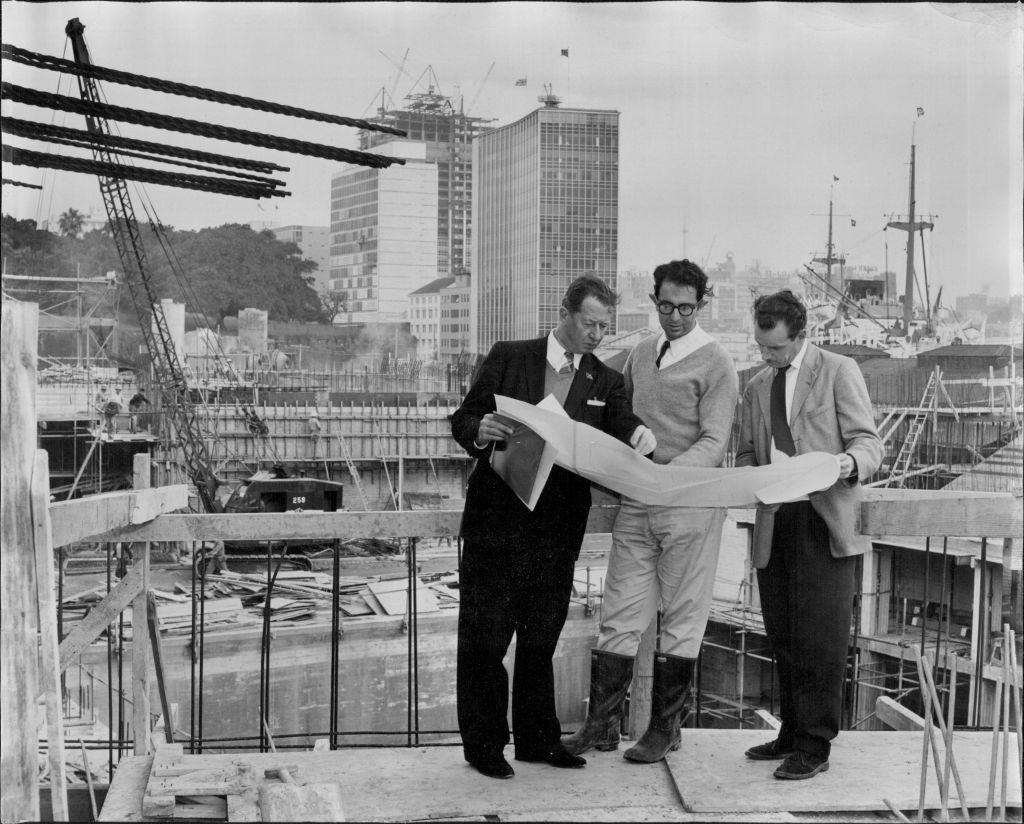 Left to right: R. J. Thomson, secretary of the Sydney Opera House Executive Committee - Mr. A. Levy, resident engineer - and Mr. O. Skipper-Nielsen, President architect with the plan of the major hall stage which is shown behind them, 1961