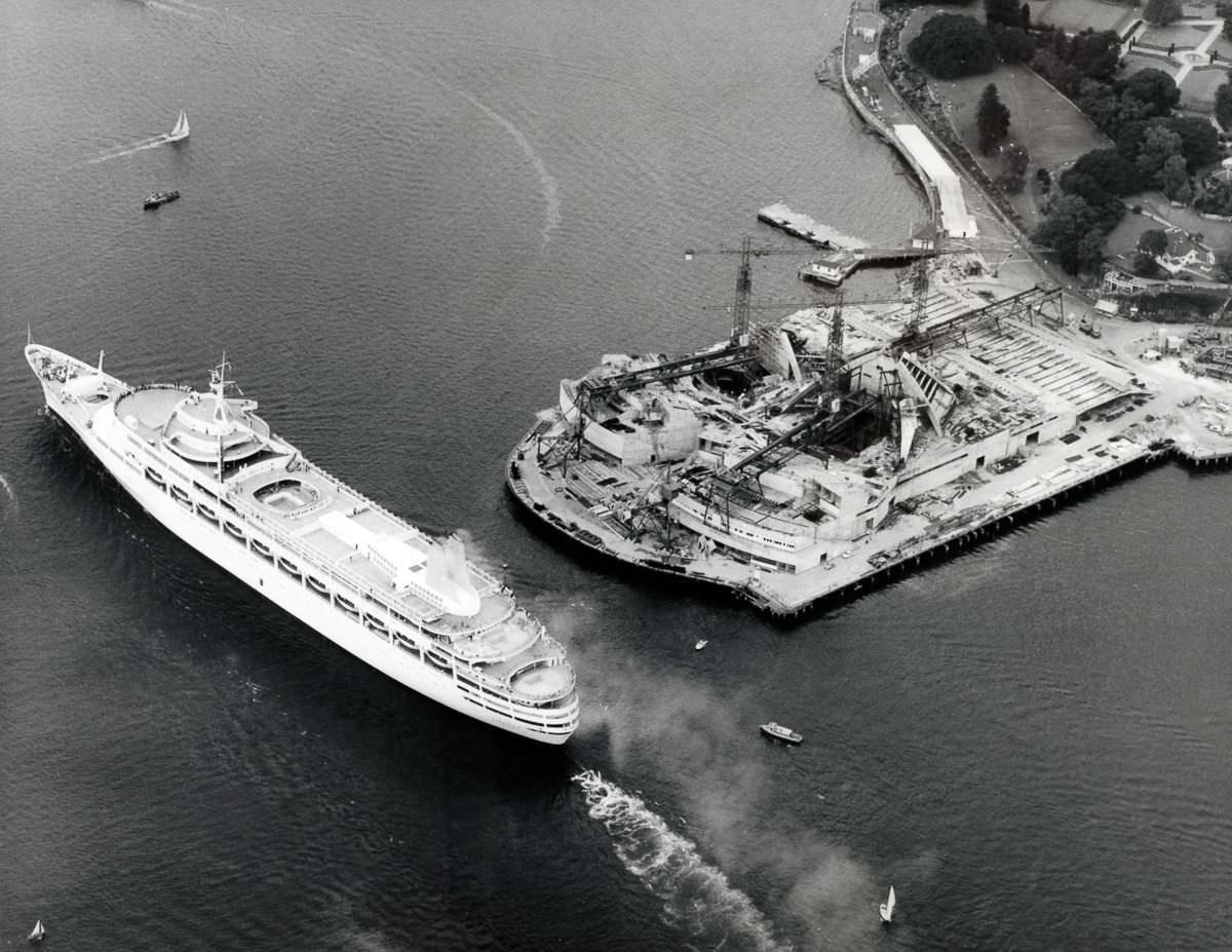 "The ocean liner ""Canberra"" passes the construction work on the Sydney Opera House, 1961."