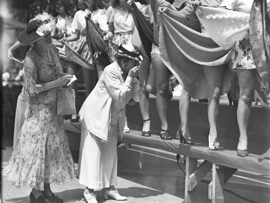 A pair of female judges examine the legs of women who are holding up their skirts during an unspecified beauty contest in New York