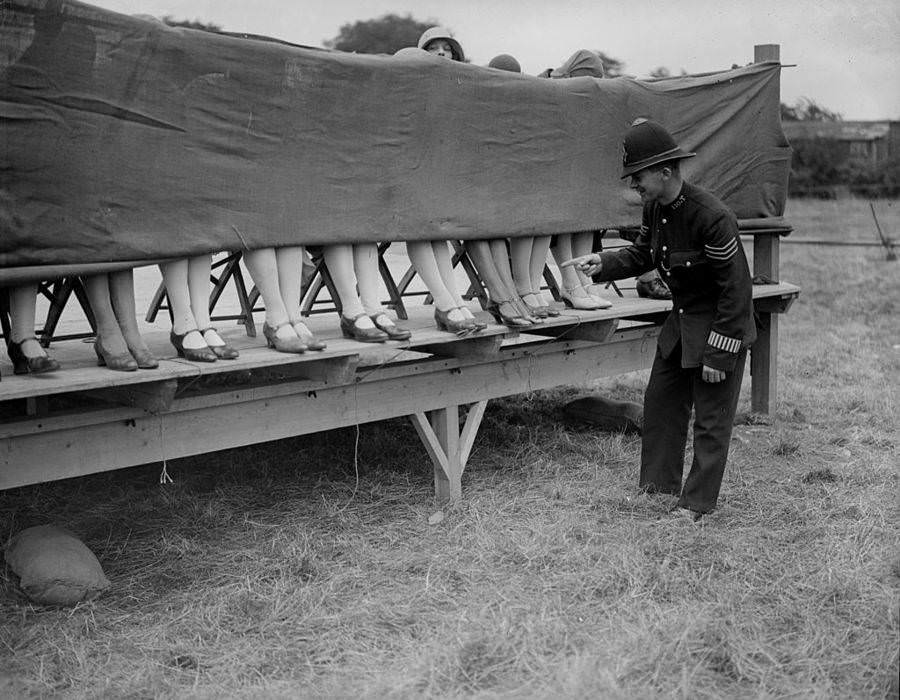A policeman judges an ankle competition in Hounslow, London, 1930