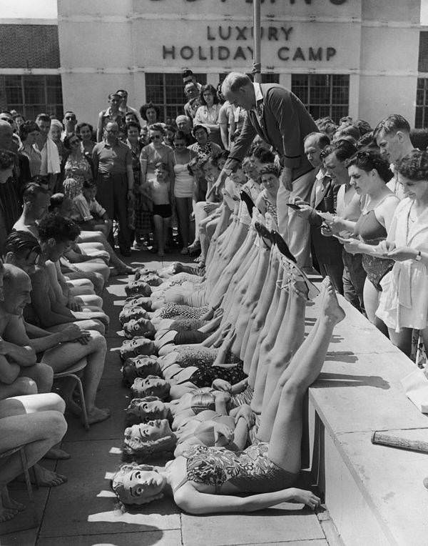 Beauty contestants are judged solely on their figures, thanks to the introduction of papier mache masks, at Butlin's holiday camp in Clacton-on-Sea, England, 1952