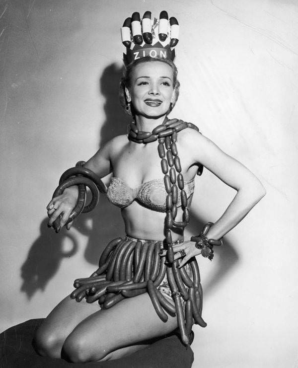 Actor Geene Courtney models a scarf, skirt, bracelets, and a crown made from hot dogs, frankfurters, and kielbasa in her role as Queen of National Hot Dog Week, as selected by the Zion Meat Products Company, 1955