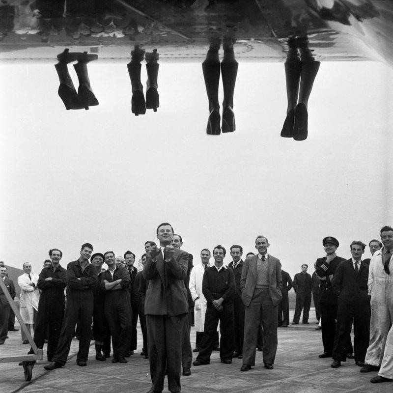The legs of contestants being judged in a Miss World beauty pageant dangle over the side of a plane while staff stands below, England, 1953.
