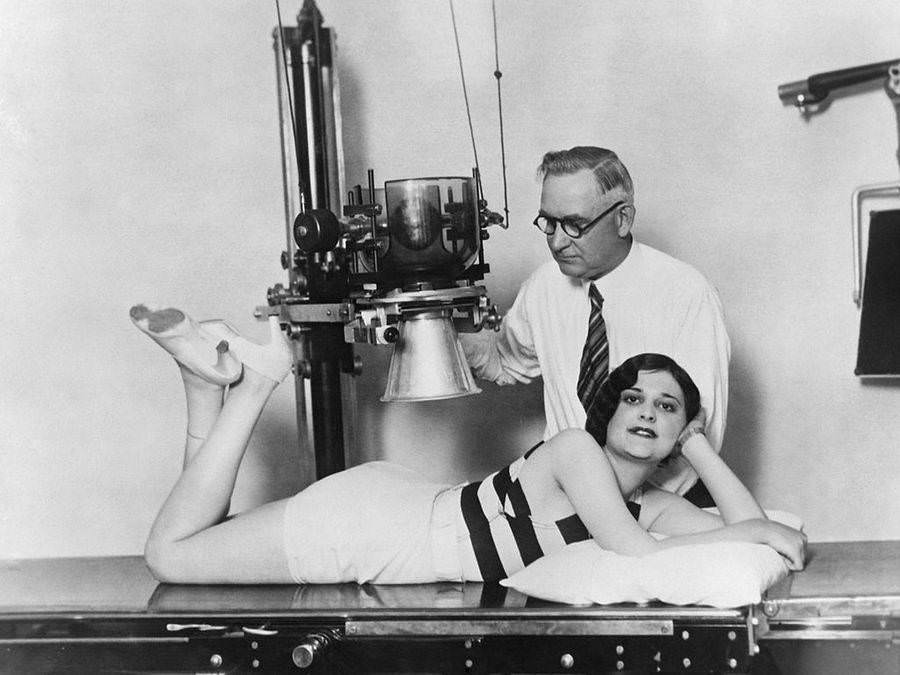 Ruth Hurschler, a contestant in a Perfect Back contest, is examined and X-rayed by a chiropractor in the final stage of the competition, Los Angeles, Circa 1930.