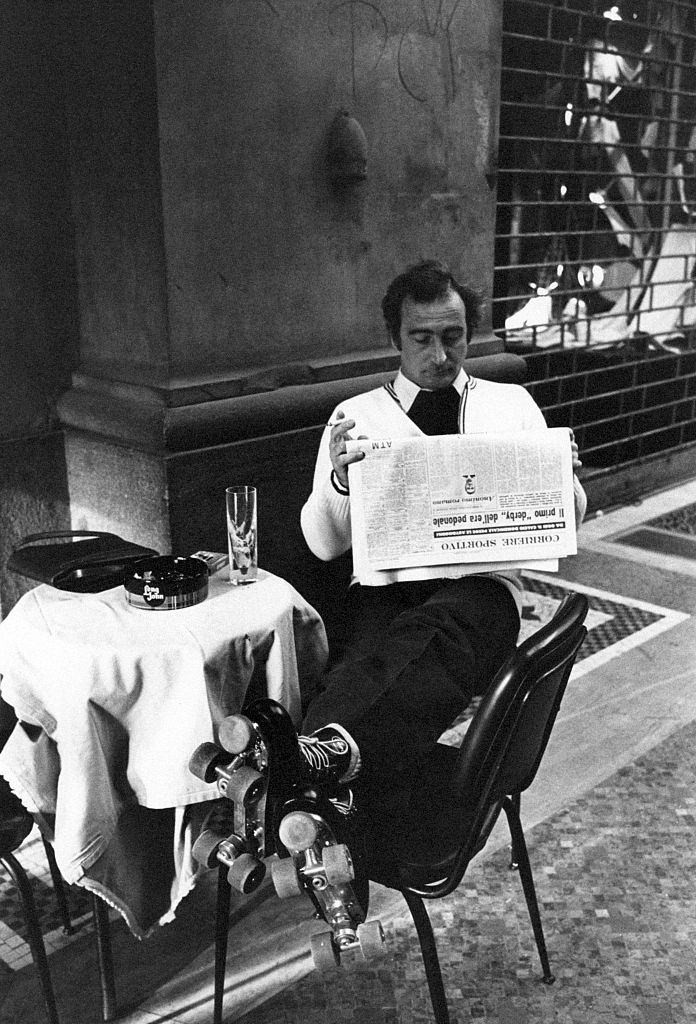 A man in roller skates reading a page from Corriere sportivo seated at the table in a caf on the first Italian walking sunday due to the oil crisis. Milan, 2nd December 1973