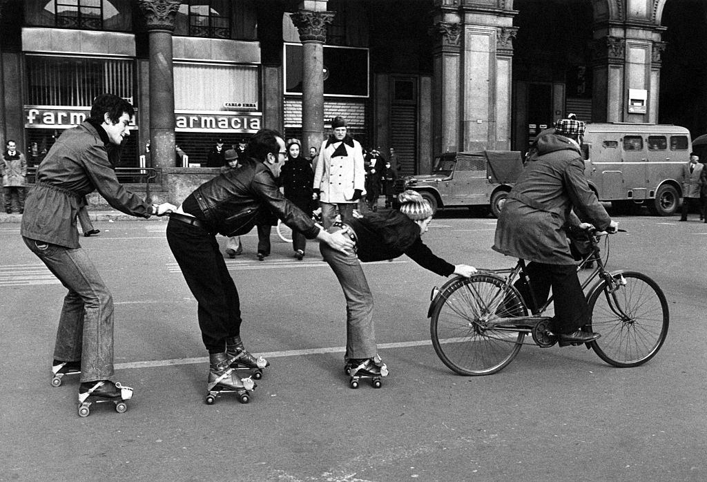 A man in bicycle drawing a little girl and two boys in roller skates on Piazza del Duomo during the first Italian walking sunday due to the oil crisis, 1973.