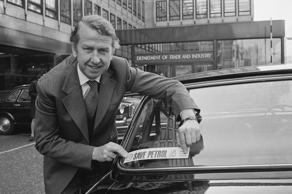 British Conservative Party politician, Peter Walker attaching a 'Save Petrol' sticker to the rear window of a car, London, November 1973.