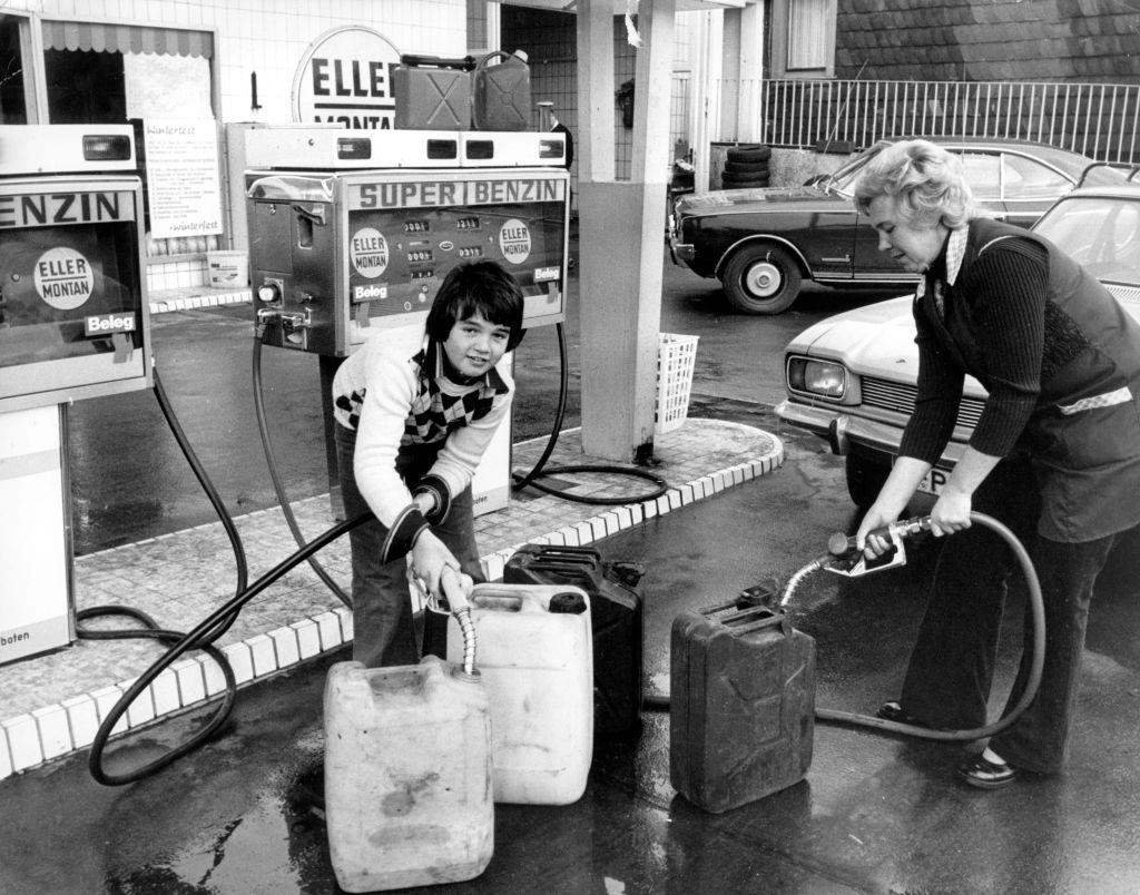 A woman and a boy fill petrol canisters with petrol at a petrol station on the 7th of November in 1973.