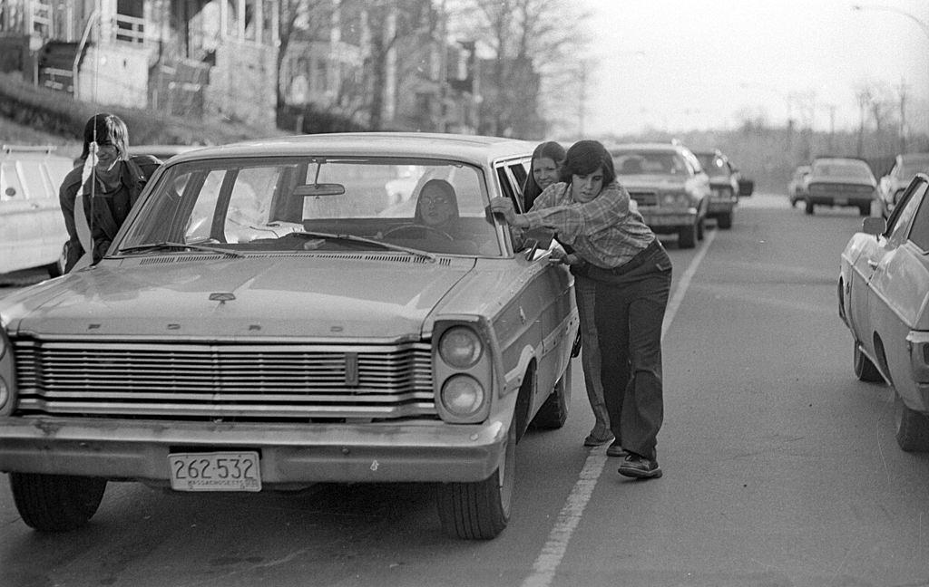 Drivers push cars to gas station during 'oil crisis,' Roslindale, Boston, Massachusetts, 1973.