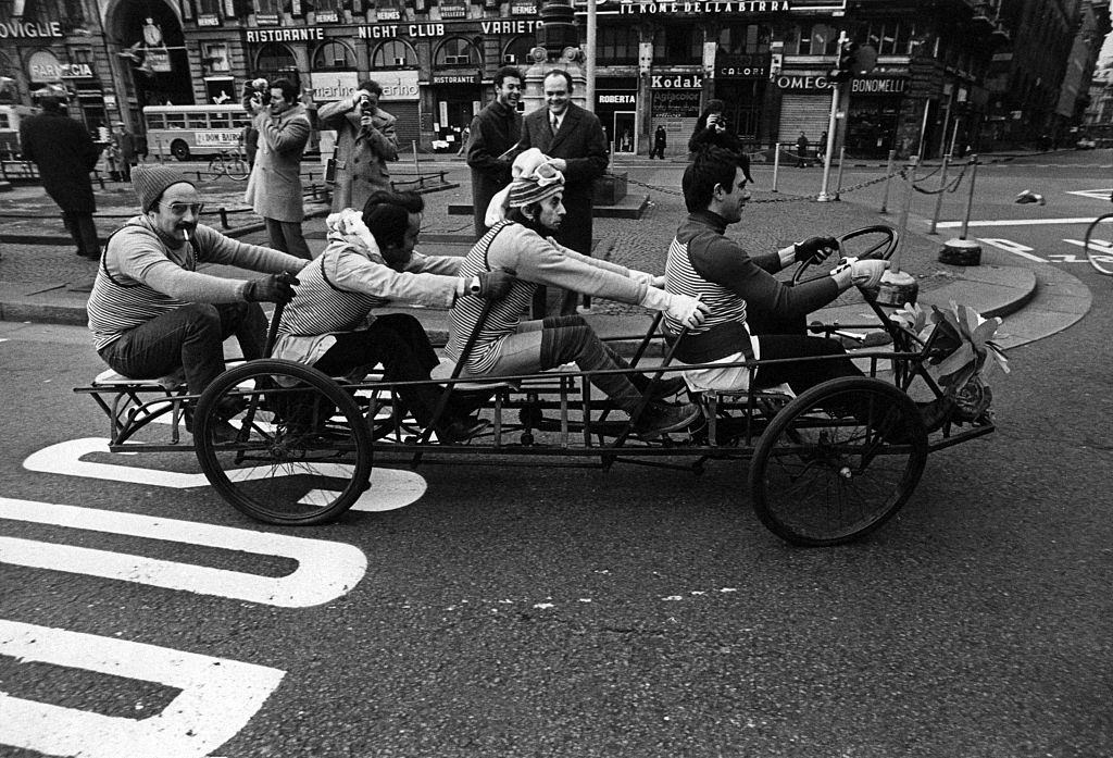 Four men on a tandem bicycle crossing Piazza del Duomo during the first Italian walking sunday due to the oil crisis. Milan, 2nd December 1973
