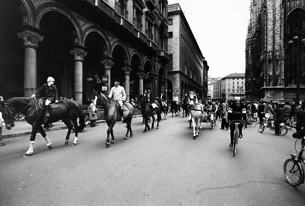 Some people riding horses, gigs and bicycles across Piazza del Duomo during the first Italian walking sunday due to the oil crisis.