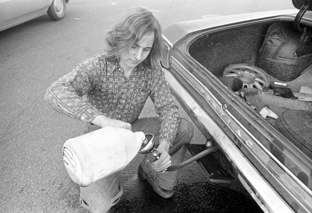 Motorist pours gas into car from jug during 'oil crisis,' Boston, Massachusetts, 1973.