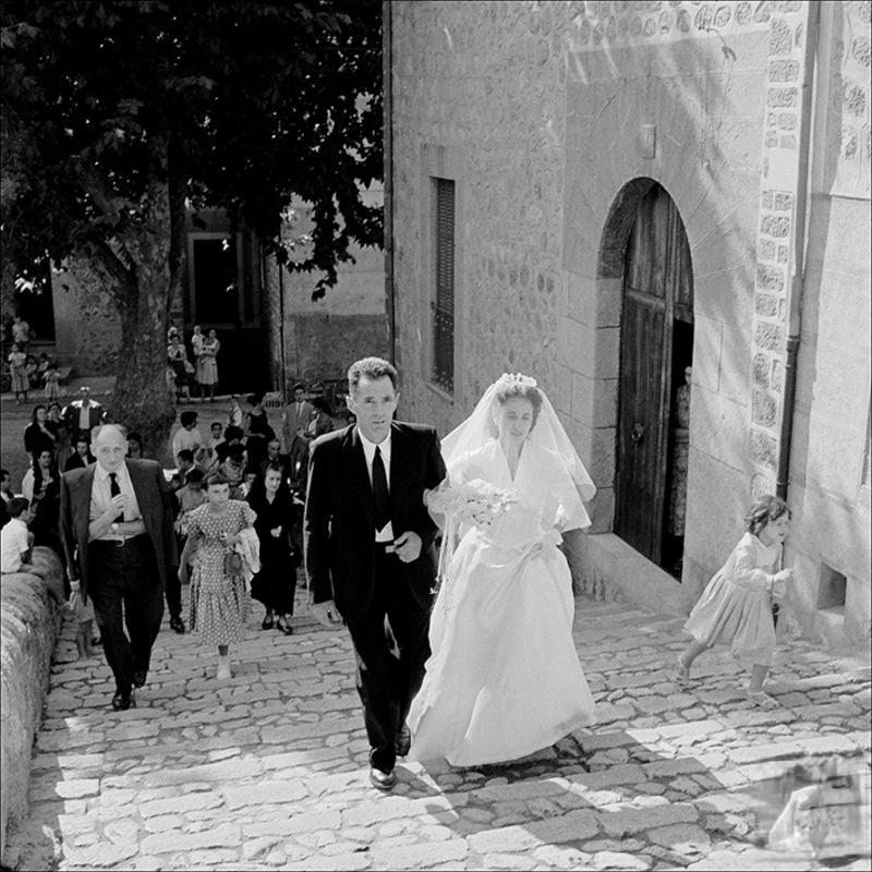 Man accompanying a bride with people in the background, 1956