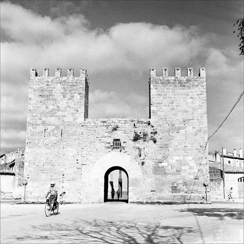 Man with a bicycle at the door from the wharf of Alcúdia, 1956