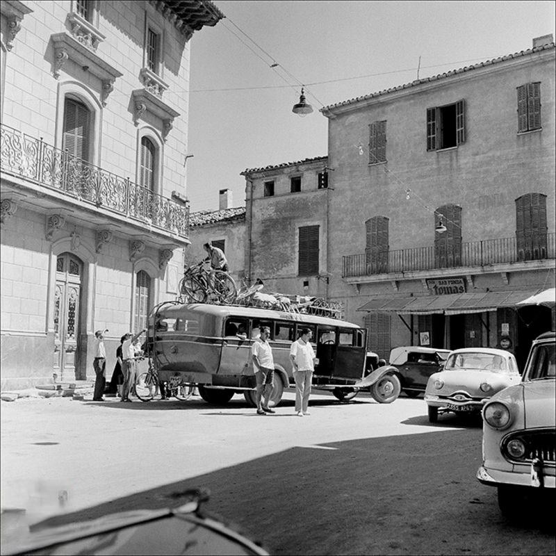 Men and cars on a street in Alcudia, 1956