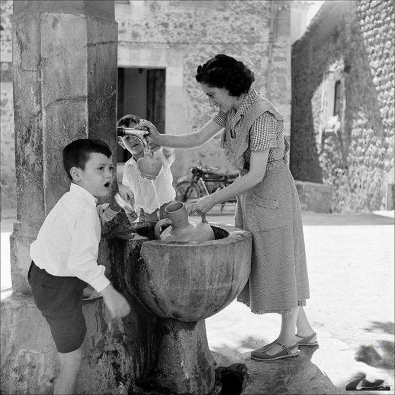 Woman removing water from a fountain with children, 1956