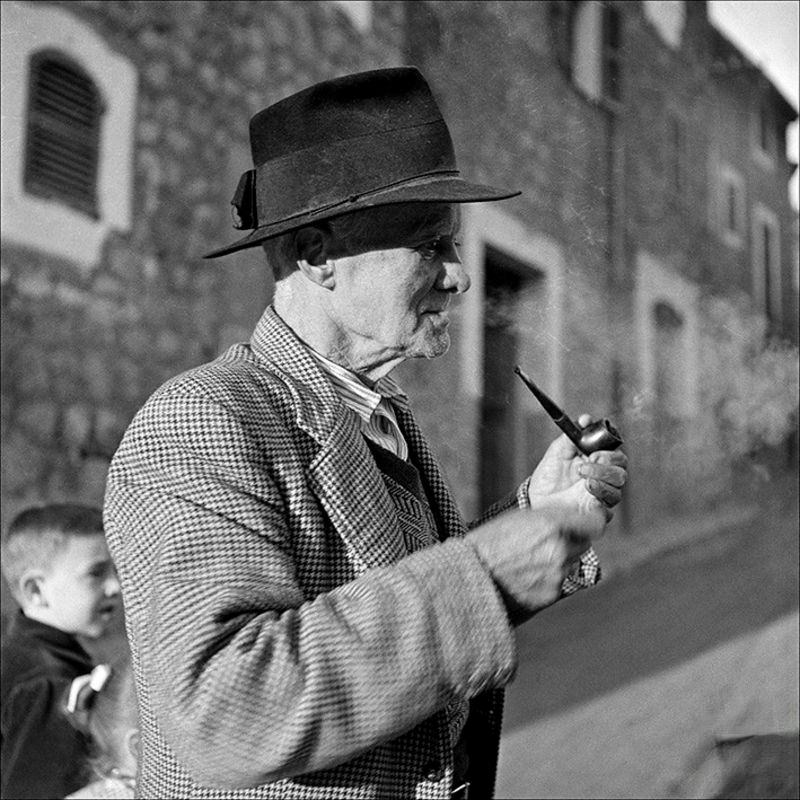 An old man smoking in the street and children in the background, 1956