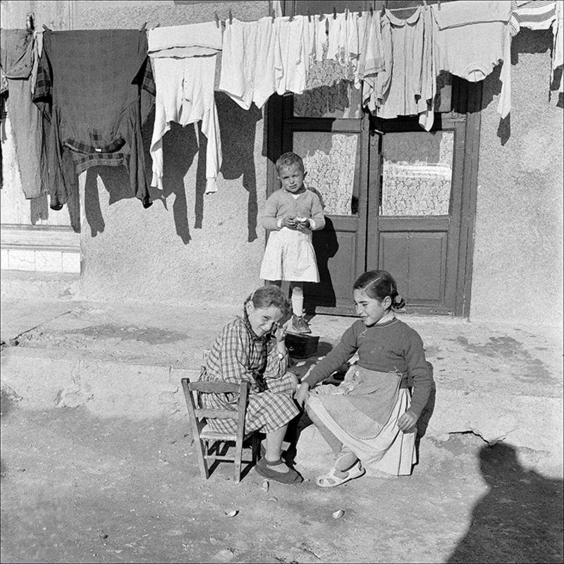 Children with clothes hanging in the background, 1956