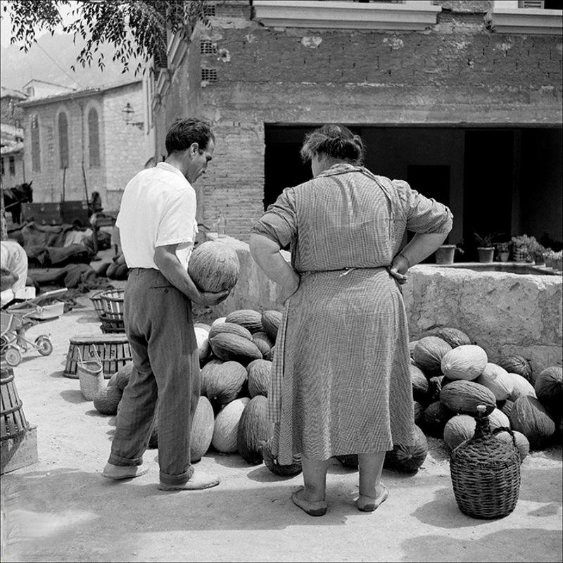 Man and woman in a stall of melons, 1956