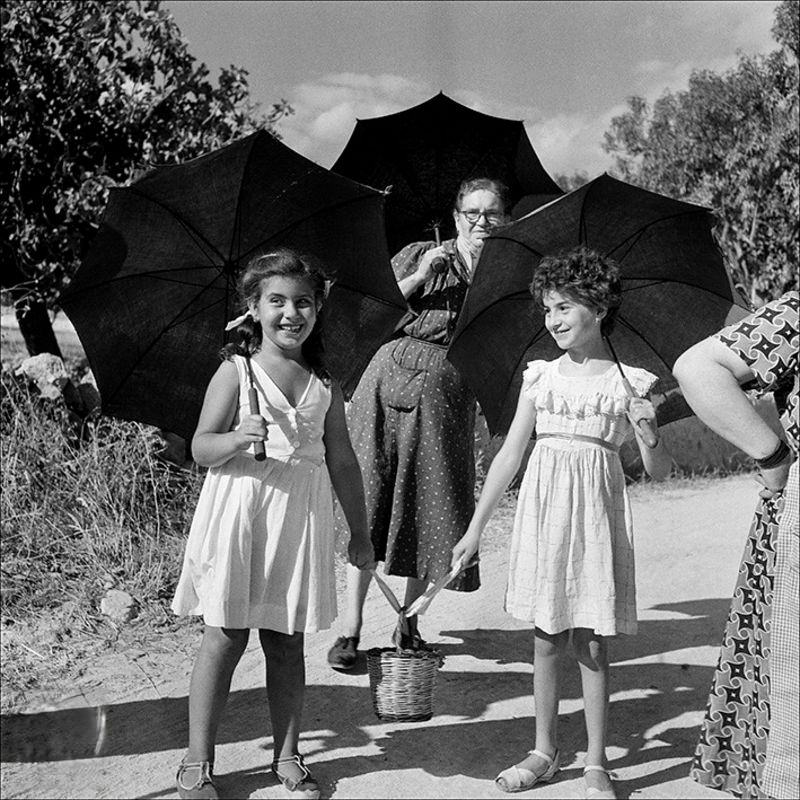 Two dolls and a woman walking with umbrellas, 1956