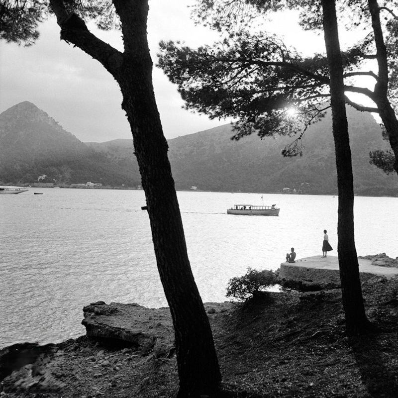 Two people by the sea with boat and mountains in the background, 1956