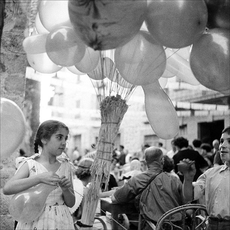 Portrait of a little girl with balloons on the street, 1957