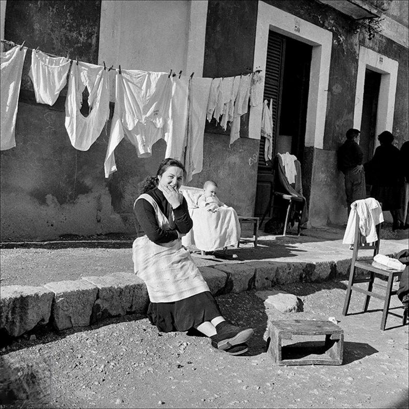 Portrait of a woman sitting with her child and clothes in the background, 1957