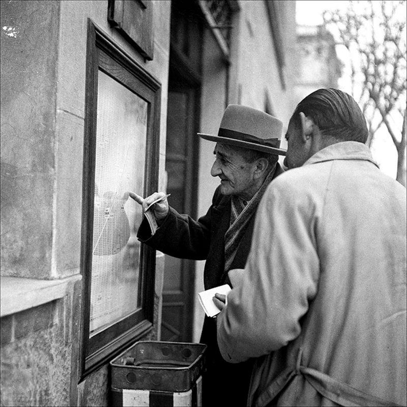 Two men looking at lottery results, 1957