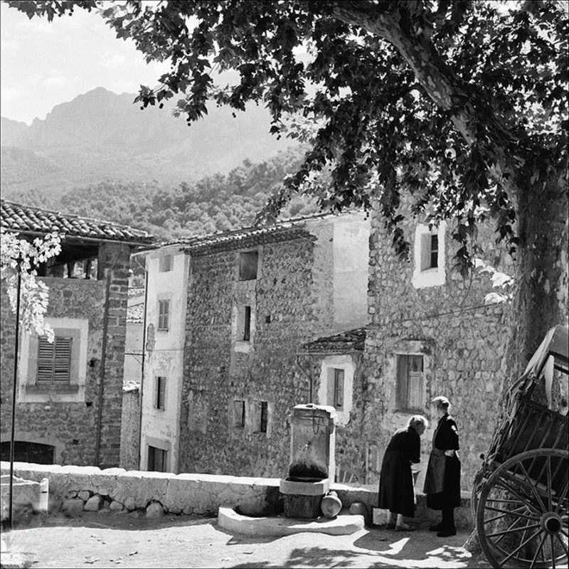 Two women picking up water in a Fornalutx square, 1957