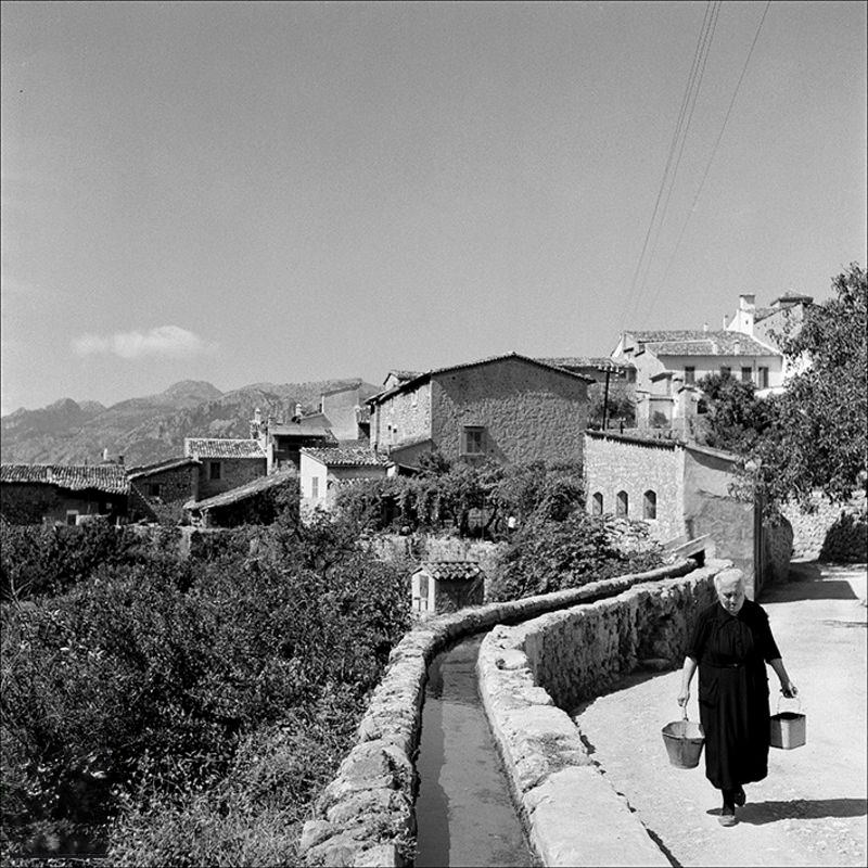 Views of the town and woman walking next to a canal, 1957