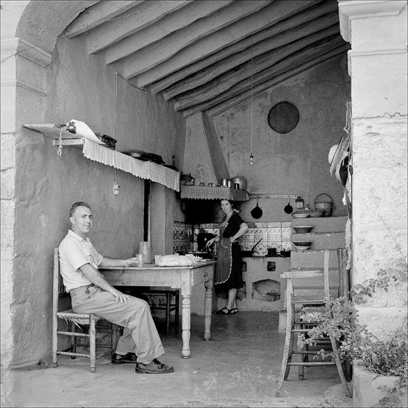 Traditional open kitchen with seated man and woman in the kitchen background, 1958