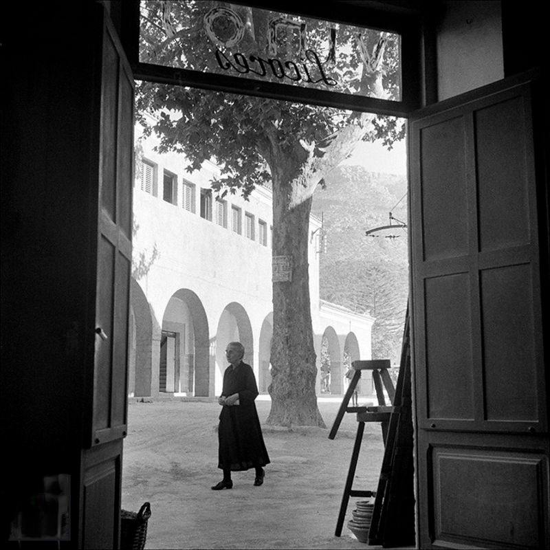 Lady walking from the inside of a wine shop, 1956