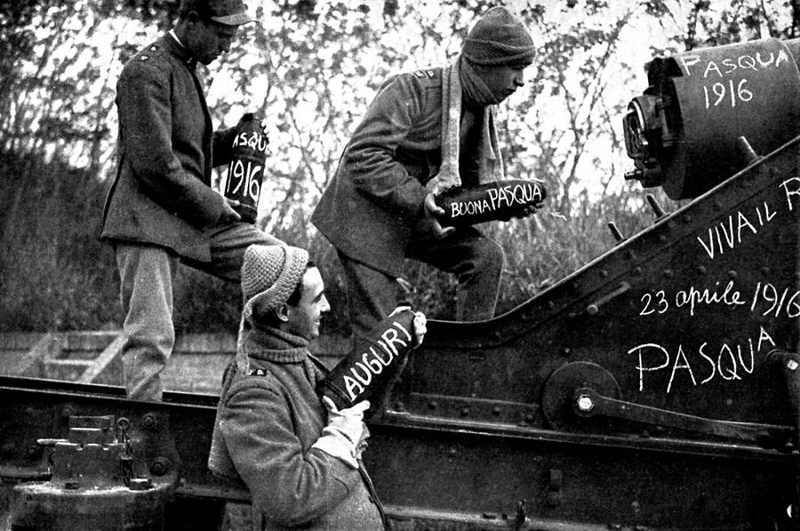 Italian artillery gunners load shells decorated with Easter messages. 1916.