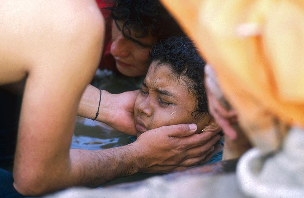 A rescuer helps Omayra Sánchez who was caught in a lahar as it flowed from the erupting Nevado del Ruiz volcano in Colombia.