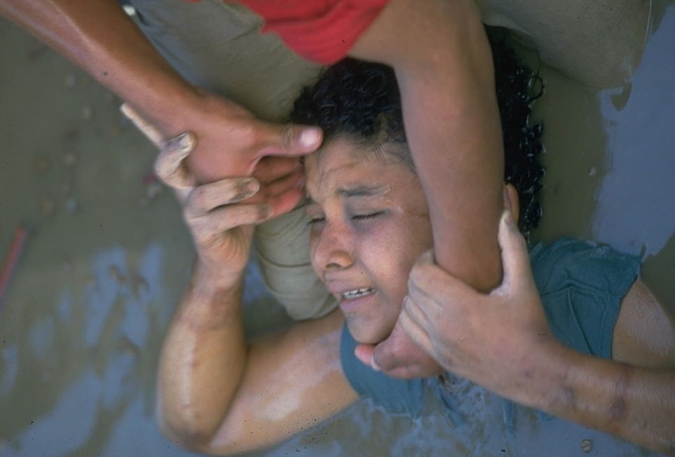 A rescuer trying to pull Omayra Sánchez.