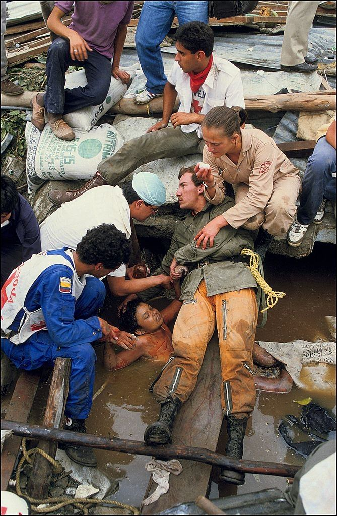 Rescuers trying to pull Omayra Sánchez, but her legs were trapped a giant vat of debris and neck-deep water.