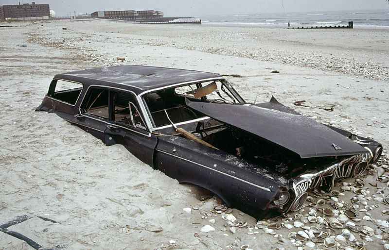 Half buried early 1960s Dodge Polara station wagon on the beach at the ocean side of Breezy Point in Queens, an abandoned apartment building at left distance, 1973