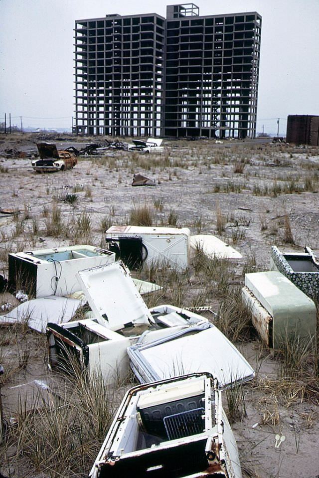 Skeleton of apartment building never completed, abandoned refrigerators and a burned out 1965 Ford Mustang, Breezy Point, Queens looking toward Brooklyn, 1973