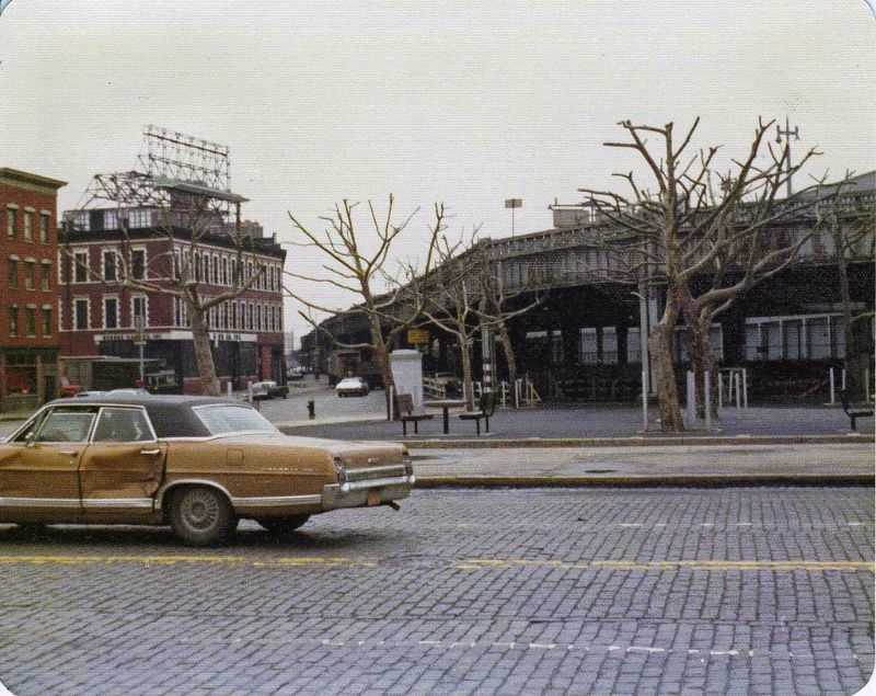 23rd St and abandoned West Side Highway, a battered Ford Galaxy 500 drives by on cobblestones, April 1975