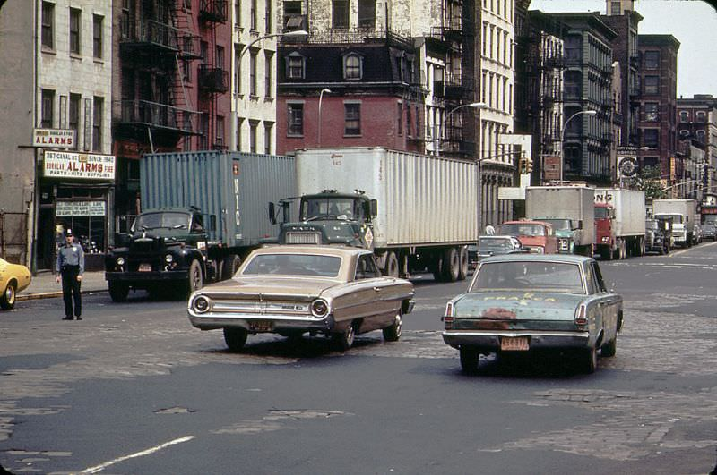 A 1960s Ford Galaxie and a battered early 1960s Plymouth Valiant cruise along Canal Street with peeling pavement, 1973