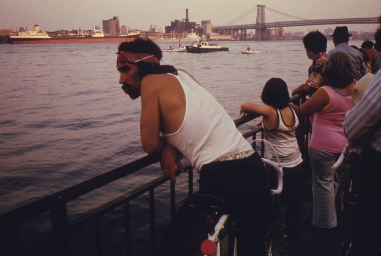 People looking at boat traffic on the East River with the Manhattan Bridge and NYC in the background, July 1974.