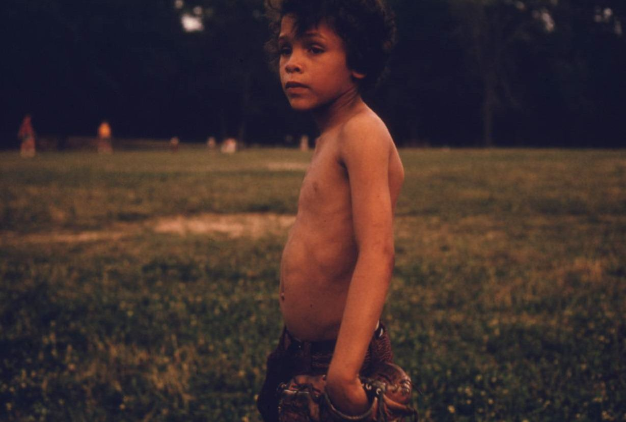 Puerto-Rican boy playing softball in Brooklyn's Hiland Park, July 1974.