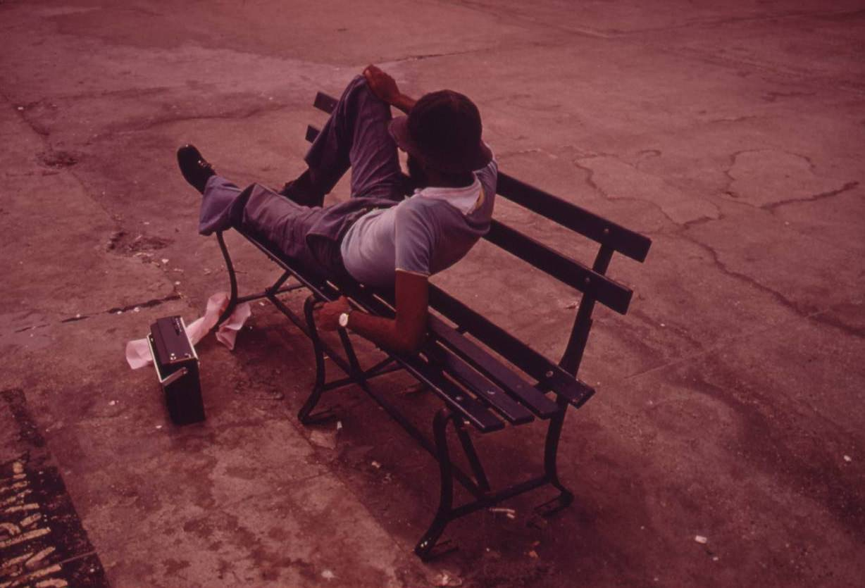 Man lounging on a park bench with his radio on the Reis Park boardwalk in NYC, July 1974.
