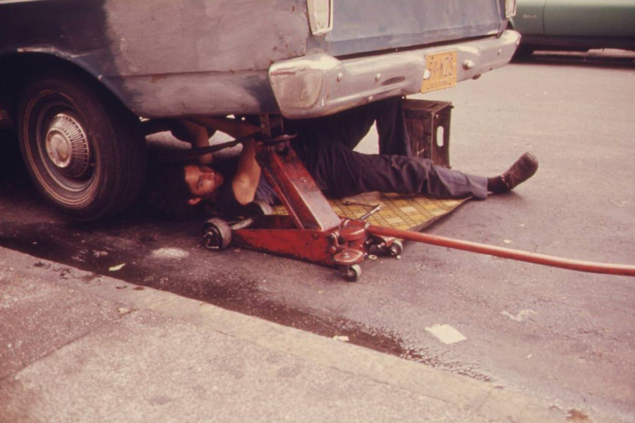 Man working on his car in Hell's Kitchen, NYC, June 1974.