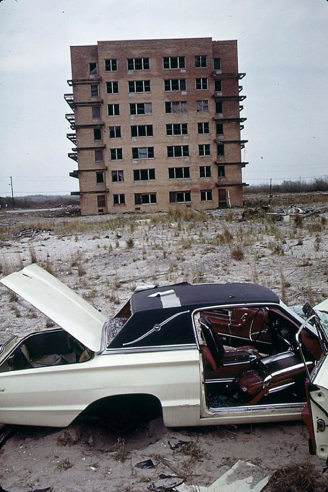 An abandoned 1960s Ford Thunderbird with broken-out windows and a torn vinyl roof, an abandoned apartment building completes the scene, Breezy Point, Queens, June 1973