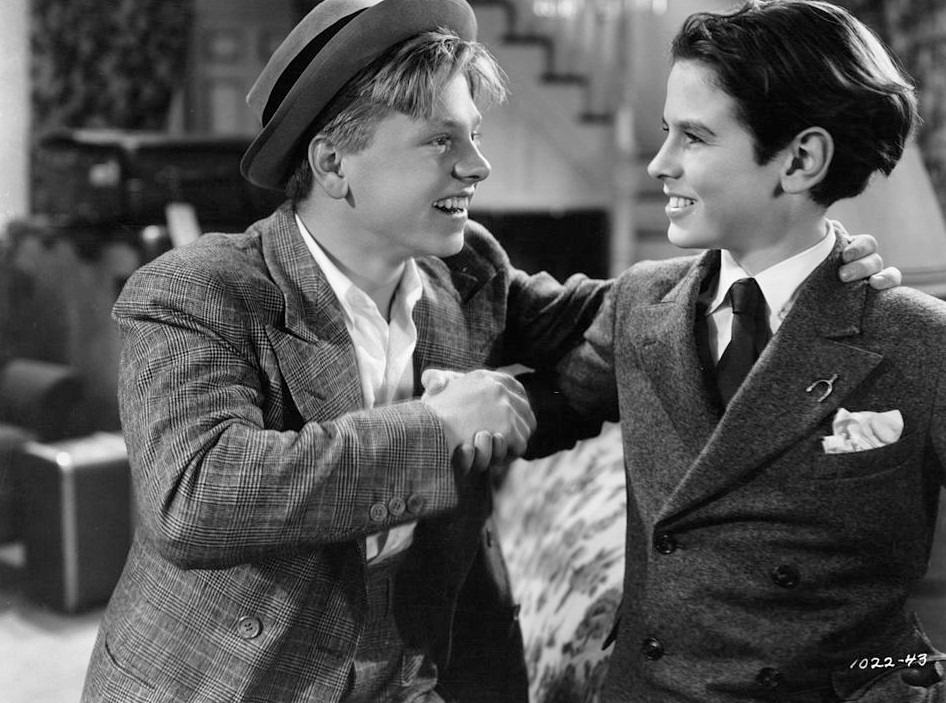 Mickey Rooney shaking Ronald Sinclair's hand in a scene from the film 'Thoroughbreds  Don't Cry', 1937. – Bygonely