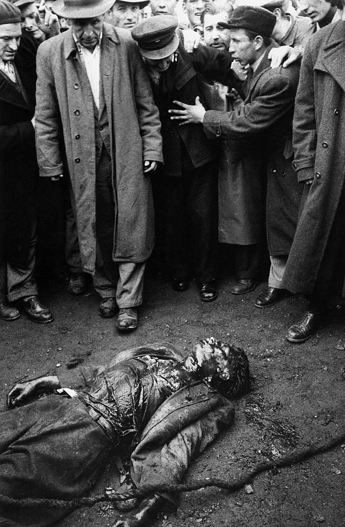 Insurgents watcing the deceased body  of a colonel of the Hungarian secret police (AVH) dead during the clashes. Budapest, November 1956
